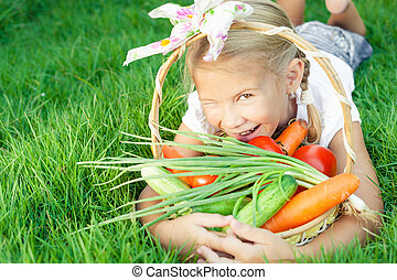 Happy little girl lying on the grass with a basket of...