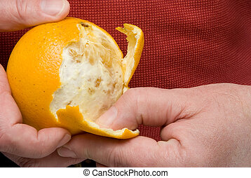 Peeling an Orange - A person in the process of peeling an...