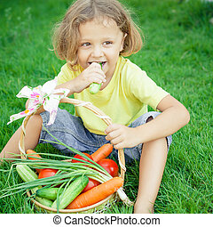 Happy little boy sitting on the grass with a basket of vegetables at the day time.