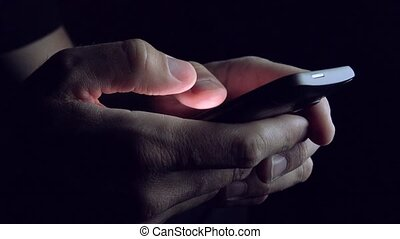 Male Hands Texting SMS Message on Mobile Smart Phone in Dark...