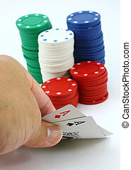 Poker player views pocket pair of aces, stack of chips