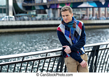 Too cold today in city. - Young man leaning on metal railing...