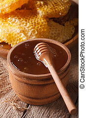 Delicious golden honey in a wooden bowl with a stick...