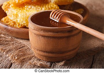 Fresh honey in a wooden bowl and honeycomb, horizontal -...