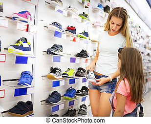 Mother and daughter shopping for shoes