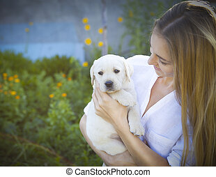 Close up of woman in white blouse with puppy of labrador