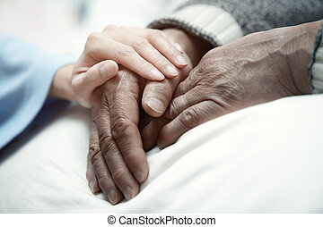 Care - Hand of woman touching senior man in clinic