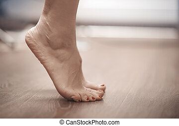 Woman tiptoeing - Feet of woman standing on tiptoe at home