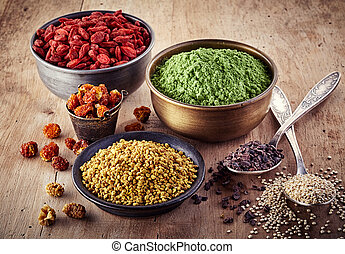 Superfood - Bowls and spoons of various superfood on wooden...