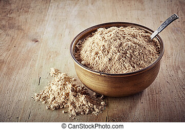 maca powder - Bowl of maca powder on wooden background