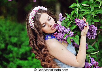 beautiful woman in a spring park smelling the lilacs