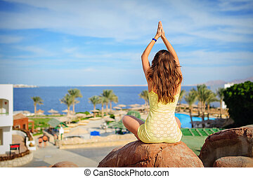woman is engaged in yoga on a background of the sea.