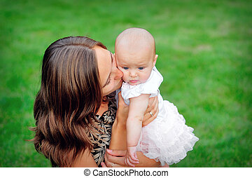 young mother kissing her baby daughter.