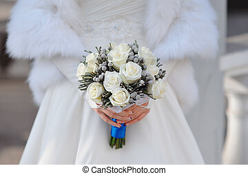white wedding bouquet of roses in hands of the bride