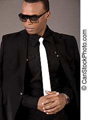 Serious black business man with sunglasses on grey...