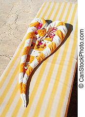heart of towels with flowers on a lounger.