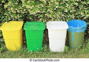 bins  - colored recycling bins with green hedge background