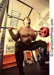 squats - Handsome muscular man with weight training...