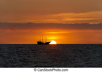 Pirate Ship Sunset - Pirate ship sunset is sailing at sea...