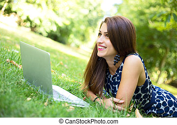 laptop outdoors - young woman using her laptop in the park