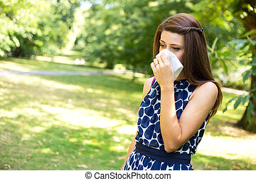 allergic - young woman with hay fever blowing her nose