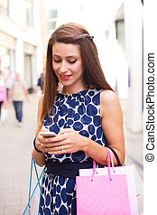 shopping girl texting - young woman using her phone while...