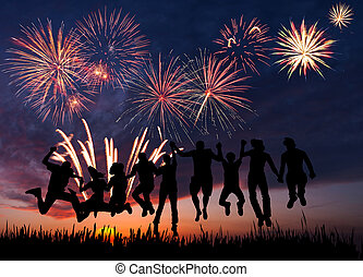 Fireworks in honor of holiday - Silhouettes of happy people...
