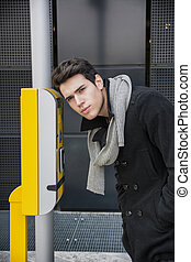 Handsome stylish young man bending down to talk on speaker...
