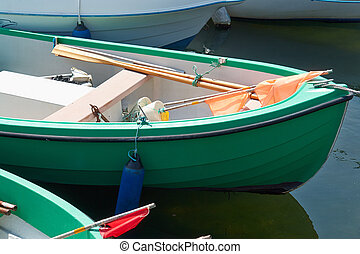 Green small fishing boat dinghy with equipment in a port...