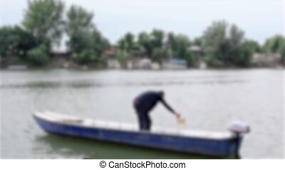 Man in boat - Blurred view on man in his boat on river