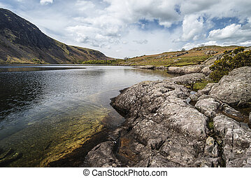 Stunning landscape of Wast Water and Lake District Peaks on Summer day reflected in lake