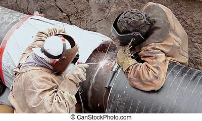 Welding team. - Welders are welding pipeline together in...