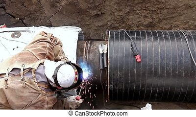 Manual Metal Arc welding. - Welder is welding pipeline to...