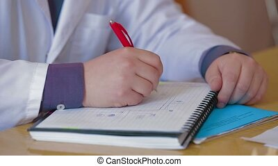Taking Notes - Medical student taking notes in a copybook