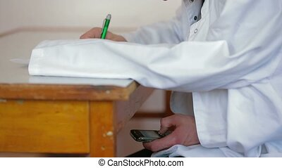 Student Using Phone - Medical student using phone on an exam...