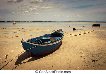 Blue Boat - Old row boat resting in the sand of a low tide...