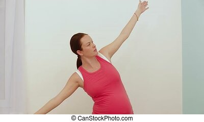 Pregnant Stretching - Pregnant woman is doing stretching...