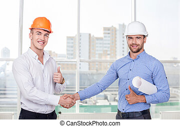 Successful young builders are congratulating each other -...