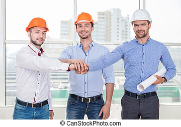 Cheerful construction crew is ready to work - Attractive...