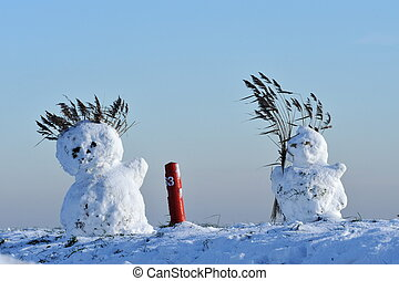 snowmen on dike in the netherlands