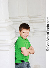 Smiling boy hands folded - Smiling boy standing at white...