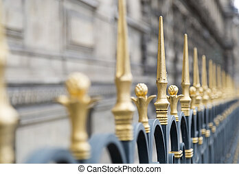 Golden Spiked Fence in with stone building in the...