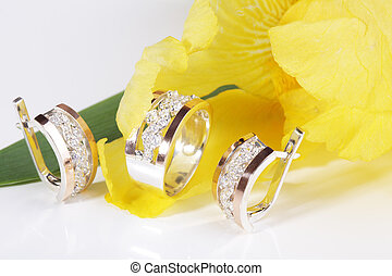 Jewelry. - Beautiful gold ring and earrings on a yellow...