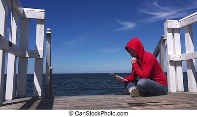 Young woman in reading at pier - Young woman reading fanzine...