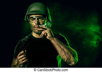 combat - Brave soldier in camouflage and helmet holding a...