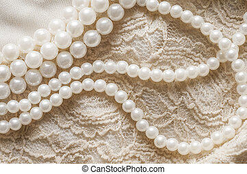 Pearl necklace on lace clothes background