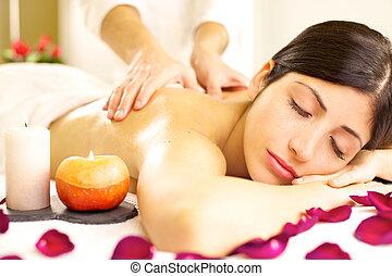 Beautiful woman receiving relaxing massage in spa