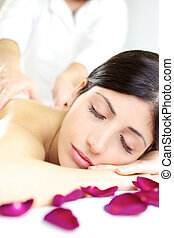 Happy woman sleeping during back massage in spa