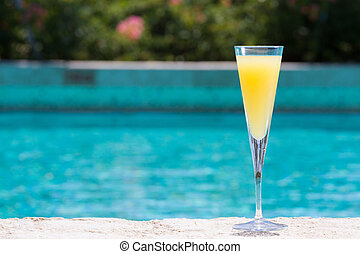 Glass of Mimosa cocktail on the pool nosing at the tropical...