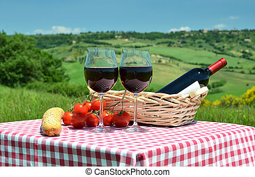 Red wine, bread and tomatoes on the chequered cloth against...